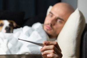 Man sick on a couch taking temperature